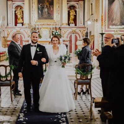 Para Młoda wychodzi zkościoła pogranatowym dywanie