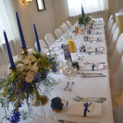 dekoracja podłużnego stołu na weselu w kolorze granatowym
