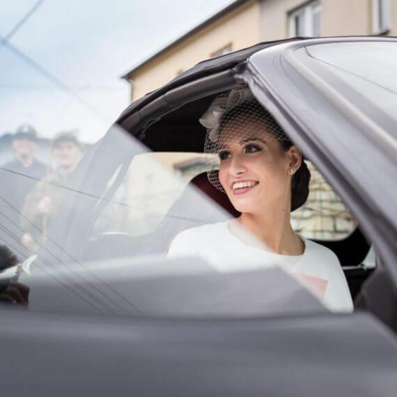 Panna Młoda zamykająca drzwi w samochodzie