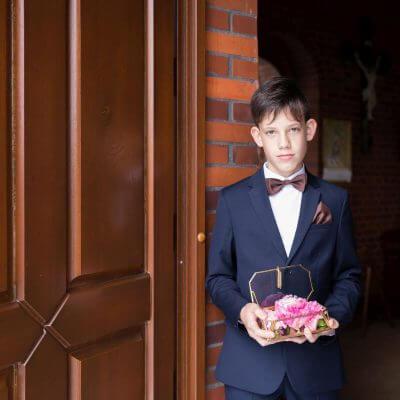 chłopiec trzymający złotą szkatułkę z obrączkami