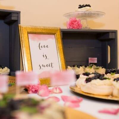 ramka z napisem love is sweet na słodkim stole