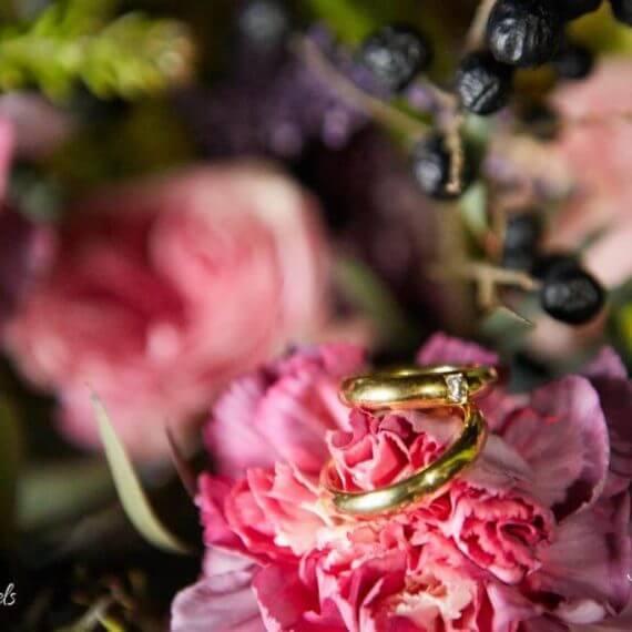 obrączki ułożone na kwiatach