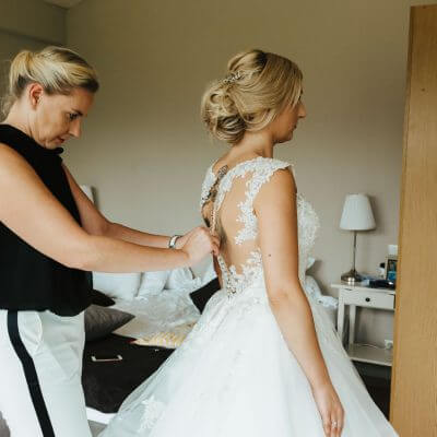 zapinanie guzików wkoronkowej sukni ślubnej