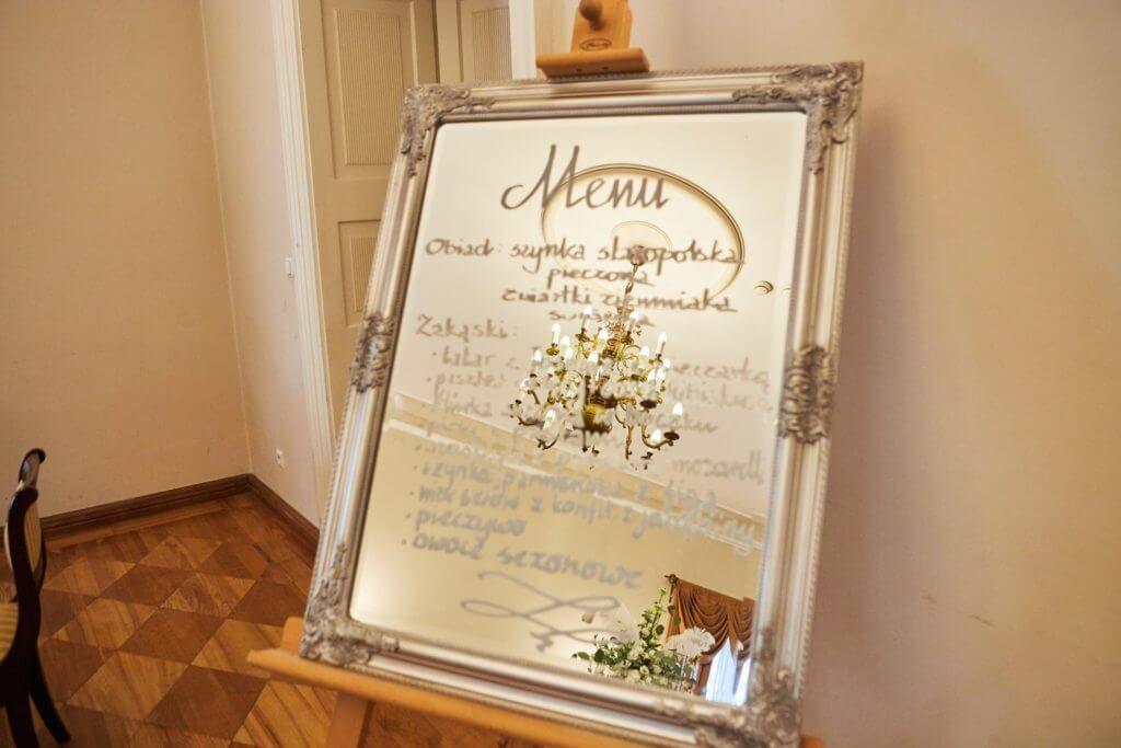 menu na lustrze w srebrnej ramie